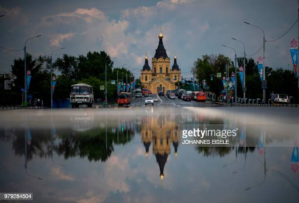 Picture taken on June 19, 2018 shows the cathedral of Alexandr Nevskiy reflected in a puddle, in the city of Nizhny Novgorod, during of the Russia...