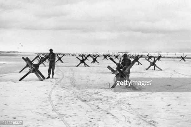 Picture taken on June 1944 on a beach in Normandy showing Royal Marine Commandos preparing to demolish the obstacles designed at preventing an Allied...