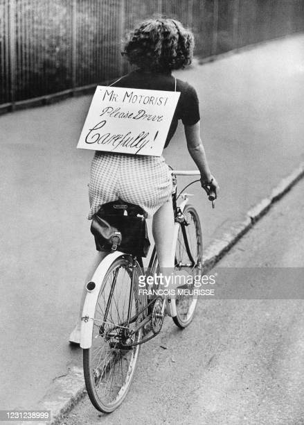 Picture taken on June 1958 somewhere in England showing a young cyclist carrying a board inviting the drivers to be careful on the road.