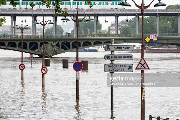A picture taken on June 2 2016 in Paris near the BirHakeim bridge shows street signs above the water on the flooded banks of the river Seine...