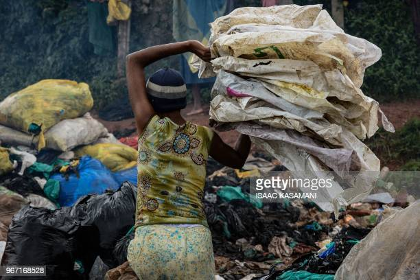 A picture taken on June 2 2018 in Kampala Uganda shows a woman cleaning plastic bags to be sold off to a factory that recycles them into home plastic...