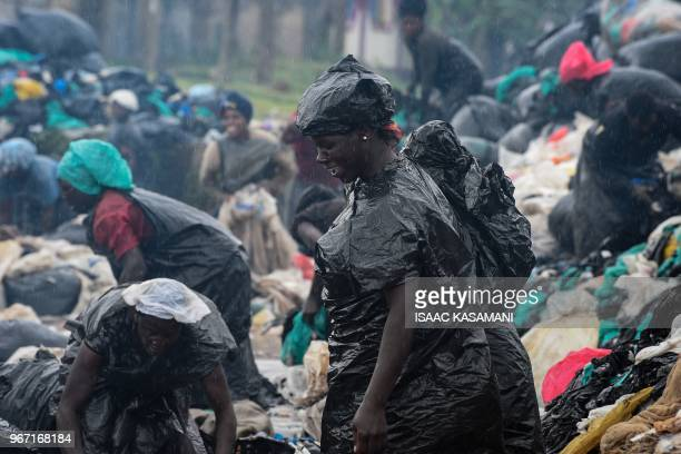 TOPSHOT A picture taken on June 2 2018 in Kampala Uganda shows women cleaning plastic bags to be sold off to a factory that recycles them into home...