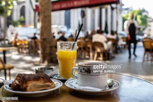 Picture taken on June 2, 2020 shows a breakfast at a terrace of a cafe in Paris, as cafes and restaurants reopen in France, while the country eases...