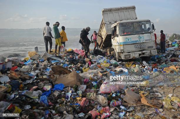 A picture taken on June 2 shows people scavenging at a dumping site in Mogadishu Somalia On June 5 2018 the United Nations mark the World Environment...