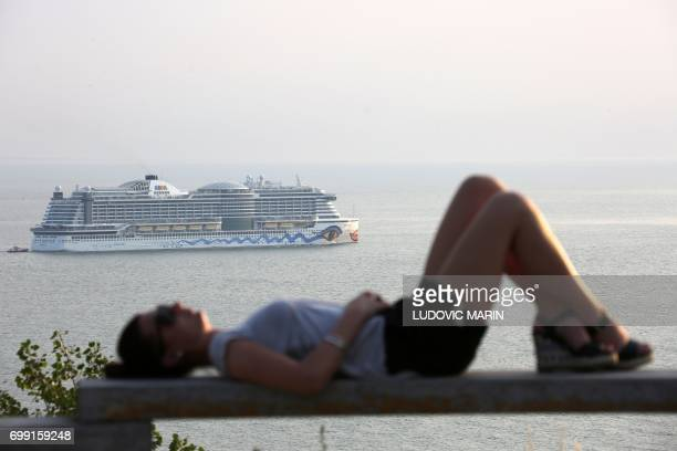 A picture taken on June 20 2017 in Le Havre shows a woman resting on a wooden guard rail as the Aida Prima cruise vessel operated by the German...