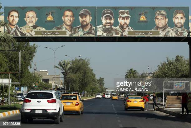 A picture taken on June 20 2018 shows a propaganda billboard for the proIran Hezbollah Brigades militia hanging on a pedestrian crossing over...