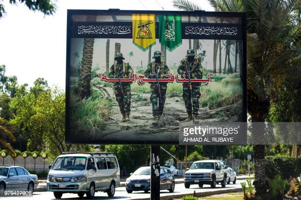 A picture taken on June 20 2018 shows a propaganda billboard for the proIran Hezbollah Brigades militia hanging over Palestine Street in the centre...