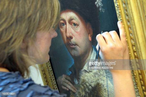 Picture taken on June 22, 2010 shows a person restoring the vernish of a painting at Ajaccio Fesch Palace on the French Mediterranean island of...
