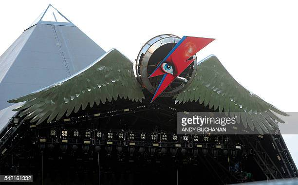 A picture taken on June 22 2016 shows A tribute to British musician David Bowie decorating the top of The Pyramid Stage at the Glastonbury Festival...