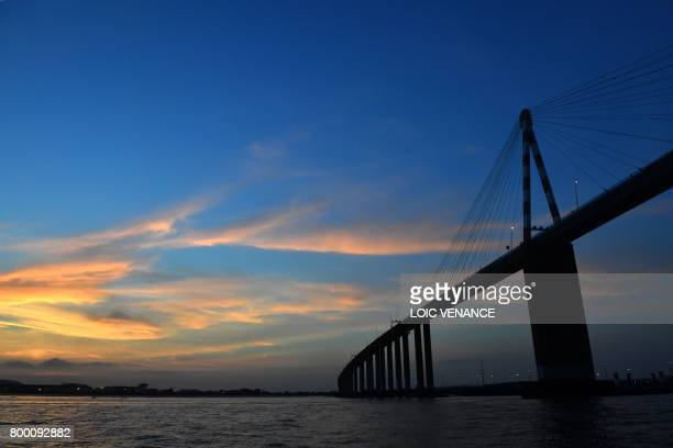 A picture taken on June 22 2017 shows the Bridge of SaintNazaire crossing the river Loire western France at sunset / AFP PHOTO / LOIC VENANCE