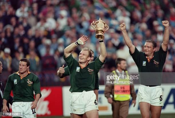 Picture taken on June 24 1995 at Johannesburg showing South African captain François Pienaar brandishing the William Webb Ellis trophy and saluting...