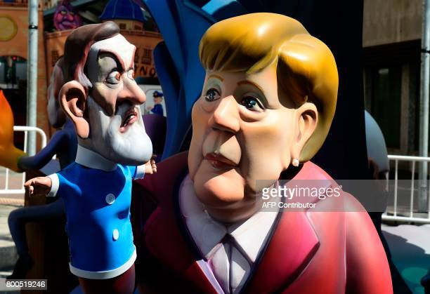 """Picture taken on June 24, 2017 shows a """"hoguera"""" representing Spanish President Mariano Rajoy as the puppet of German Chancellor Angela Merkel,..."""