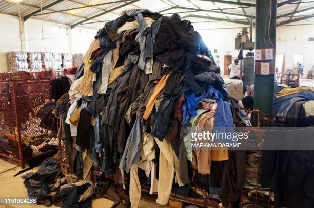 A picture taken on June 25 2019 shows a pile of secondhand clothes at the textile recycling centre of the French social enterprise Le Relais in...