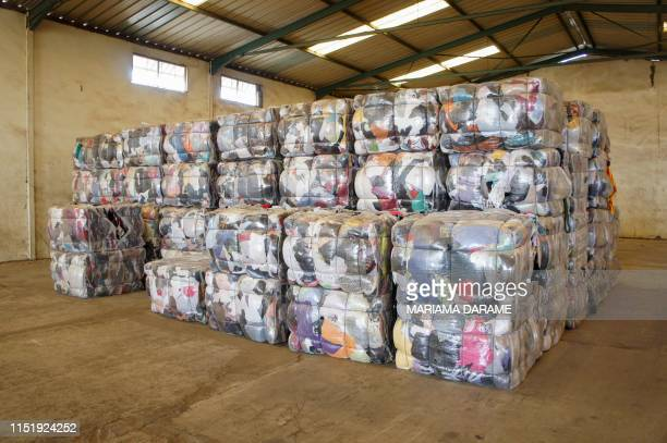 A picture taken on June 25 2019 shows bales of secondhand clothes ready to be sent to wholesalers at the textile recycling centre of the French...