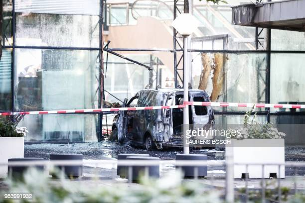 A picture taken on June 26 2018 on Basisweg street in Amsterdam shows a van that crashed through the front door of the building that houses newspaper...
