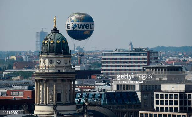 Picture taken on June 26 2019 shows the WeltBalloon touristic attraction seen behind the cupola of the Deutscher Dom at Gendarmenmarkt square...