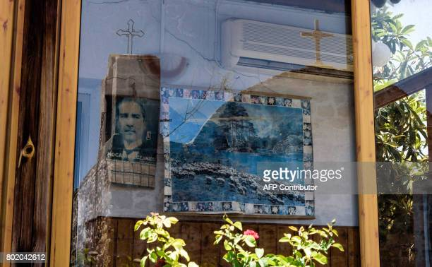A picture taken on June 27 2017 shows a reflection of a church on the glass of a window of a room with the portrait of Turkey's founder Mustafa Kemal...