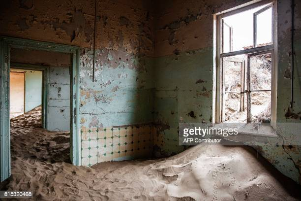 A picture taken on June 27 2017 shows an abandoned house filled with sand in the deserted mining town of Kolmanskop in Luderitz Namibia The...
