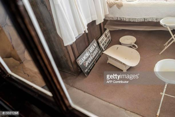A picture taken on June 27 2017 shows furniture in an abandoned house filled with sand in the deserted mining town of Kolmanskop in Luderitz Namibia...