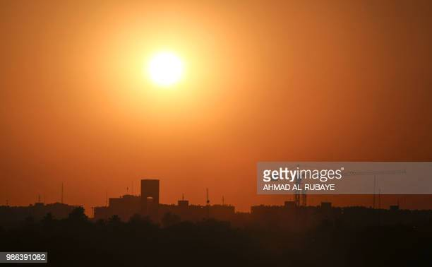 A picture taken on June 28 2018 shows a view of a sun setting past a construction crane in the Iraqi capital Baghdad's Green Zone