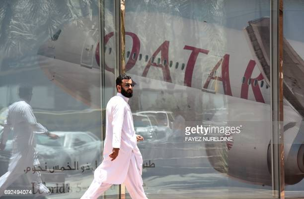 A picture taken on June 5 2017 shows a man walking past the Qatar Airways branch in the Saudi capital Riyadh after it had suspended all flights to...