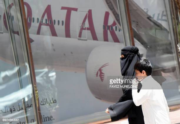 A picture taken on June 5 2017 shows a Saudi woman and a boy walking past the Qatar Airways branch in the Saudi capital Riyadh after it had suspended...