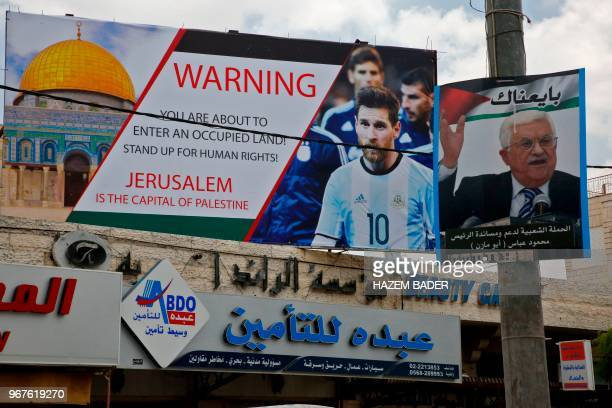 A picture taken on June 5 shows a poster erected on a main street in the West Bank town of Hebron next to a portrait of the Palestinian president...