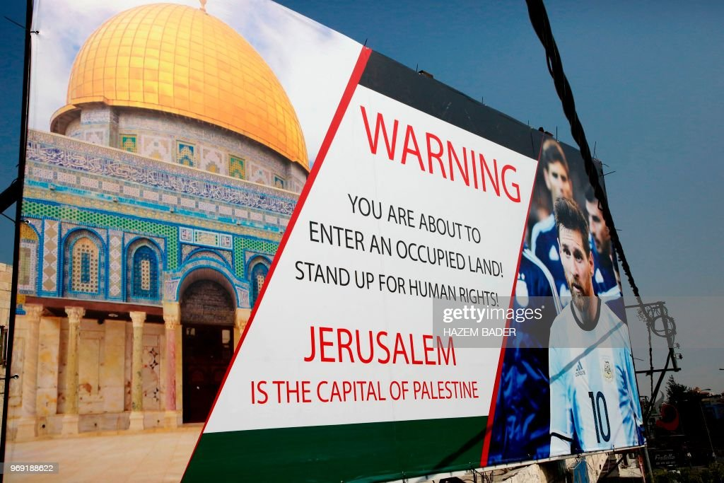 A picture taken on June 5, 2018, shows a poster erected on a main street in the West Bank town of Hebron, denouncing the upcoming friendly football match between Argentina and Israel and calling Argentina's star Lionel Messi (portrait) to boycott the match. - Palestinian football boss Jibril Rajoub, on June 3, called on Barcelona star Lionel Messi not to play in the Argentina-Israel game that is scheduled to take place in Jerusalem on June 9 and urged fans to burn their shirts if he does.