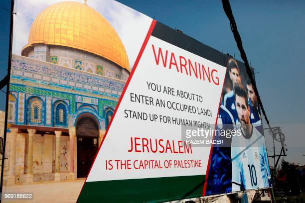 A picture taken on June 5 shows a poster erected on a main street in the West Bank town of Hebron denouncing the upcoming friendly football match...