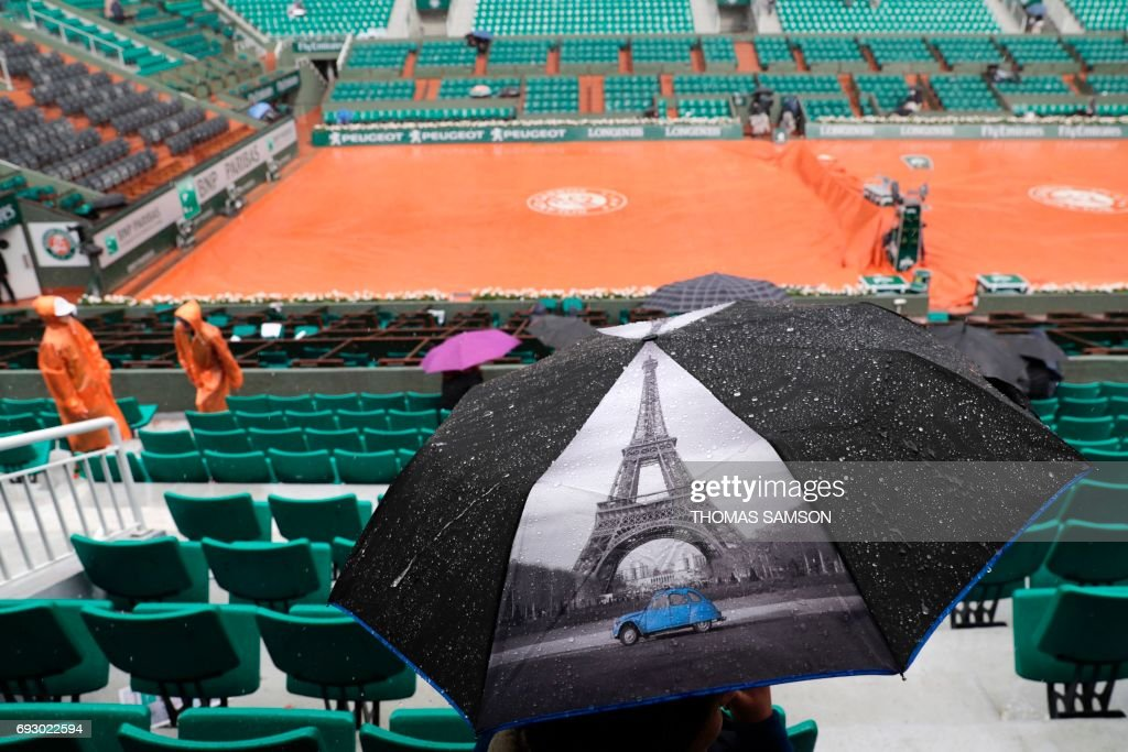 TOPSHOT - A picture taken on June 6, 2017 in Paris shows a visitor, with an umbrella featuring the Eiffel Tower, waiting under the rain for a match to resume on the Philippe Chatrier court during a downpour at the Roland Garros 2017 French tennis Open. / AFP PHOTO / Thomas Samson