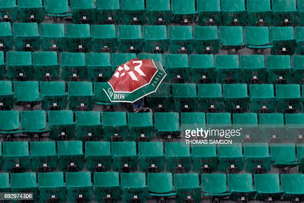 TOPSHOT A picture taken on June 6 2017 in Paris shows a visitor with an umbrella waiting under the rain for a match to resume on the Philippe...
