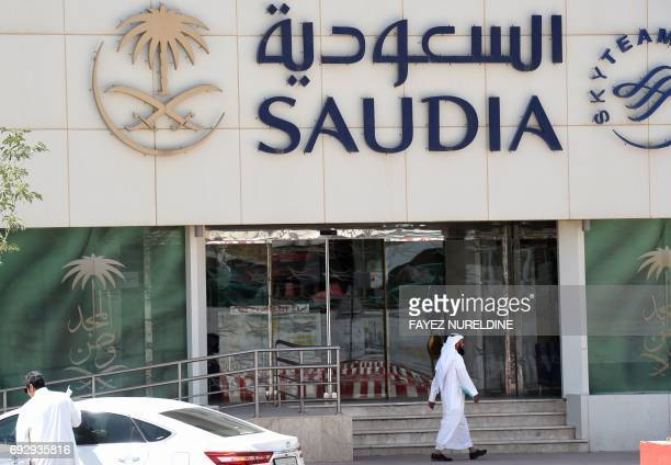 A picture taken on June 6 2017 shows a Saudi man walking past the Saudi Airlines headquarters in the capital Riyadh after it had suspended all...