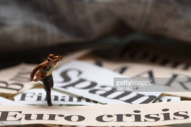 A picture taken on June 8 2012 in Paris shows a figurine and words cut from newspapers to illustrate recession crisis and financial situation in...