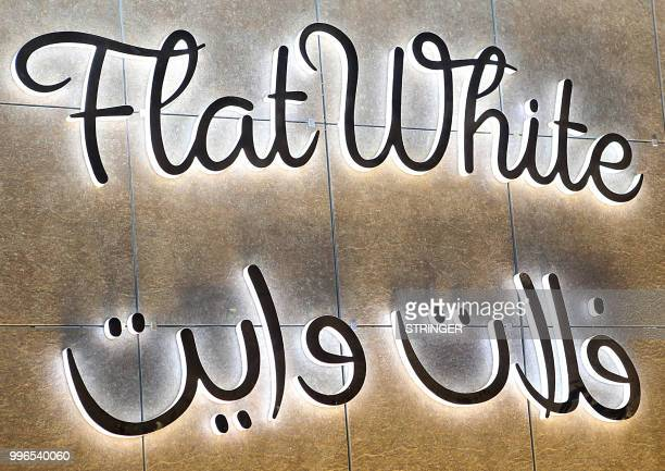 A picture taken on June 8 2018 shows the neonlit logo of the 'Flat White' cafe in the Qatari capital Doha's Tawar Mall Tawar Mall looks like any of...