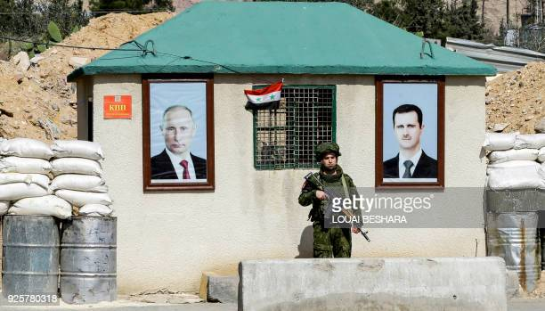 Picture taken on March 1, 2018 shows a member of the Russian military police standing guard between the portraits of Syrian President Bashar al-Assad...