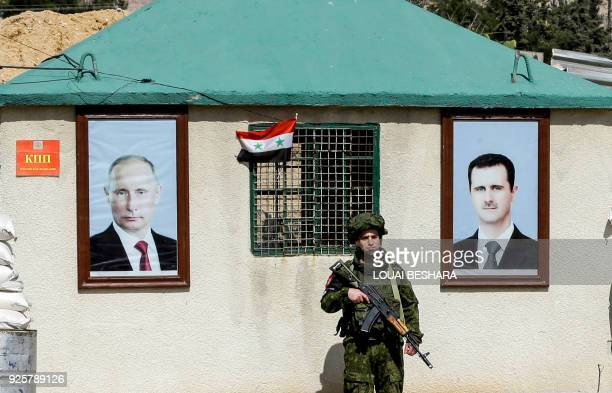 A picture taken on March 1 2018 shows a member of the Russian military police standing guard between the portraits of Syrian President Bashar alAssad...