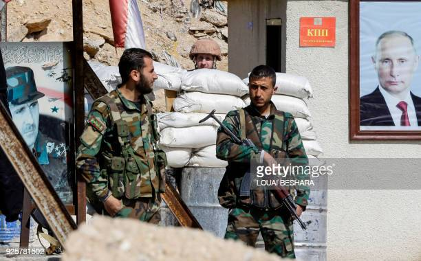 A picture taken on March 1 2018 shows members of the Syrian government forces standing guard between the portraits of Syrian President Bashar alAssad...