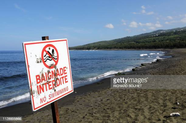 A picture taken on March 1 2019 shows a sign banning swimming at the L'EtangSale beach on the Indian Ocean island of La Reunion A fisherman was...