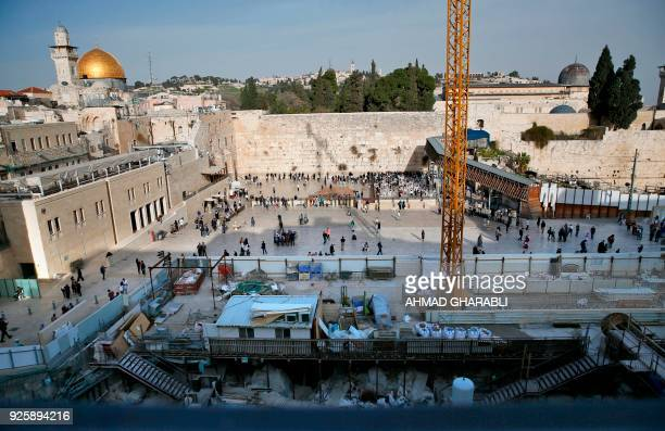 A picture taken on March 1 shows a general view of construction work in the Western Wall plaza of Jerusalem's Old City with the Dome of the Rock...