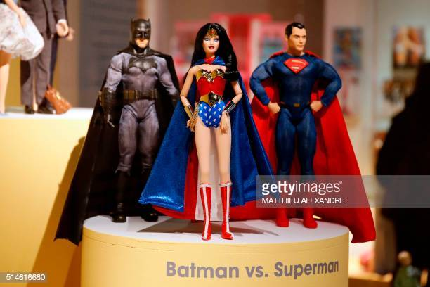 A picture taken on March 10 2016 shows Barbie dolls representing Batman Wonder Woman and Superman during the exhibition 'Barbie life of an icon' at...