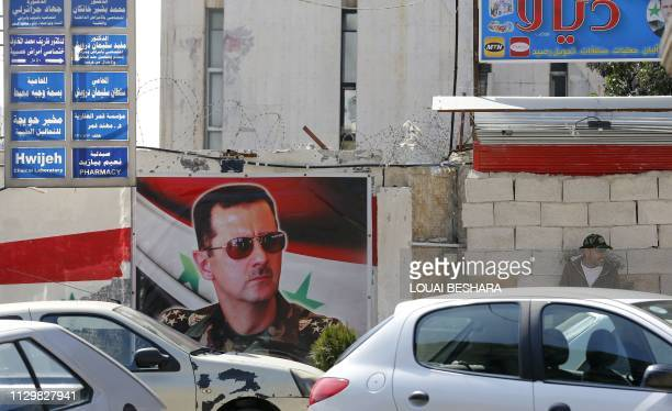 Picture taken on March 11, 2019 shows a Syrian man sitting next to a billboard bearing a portrait of President Bashar al-Assad in the capital...