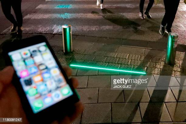 Picture taken on March 12, 2019 shows LED ground level lights installed to warn texting pedestrians before crossing the road in the coastal city of...