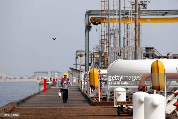 A picture taken on March 12 shows an Iranian labourer walking the platform of the oil facility in the Khark Island on the shore of the Gulf / AFP...