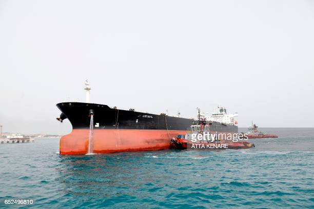 A picture taken on March 12 shows an Iranian tanker docking at the platform of the oil facility in the Khark Island on the shore of the Gulf / AFP...