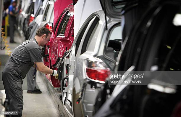 FILES A picture taken on March 13 2007 shows an employee of German car maker Opel working on the assembling of an Astra car at the Opel plant in...