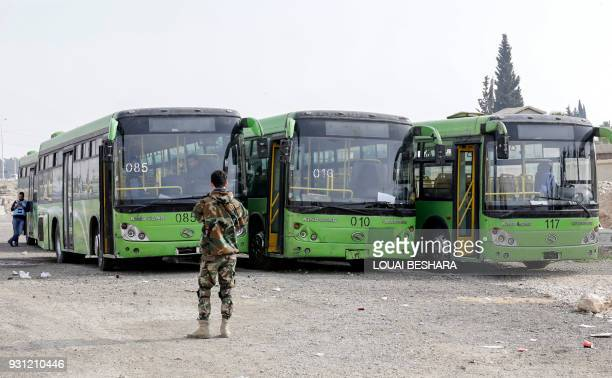 TOPSHOT A picture taken on March 13 2018 shows buses waiting to evacuate civilians on the government side of the Wafideen checkpoint on the outskirts...