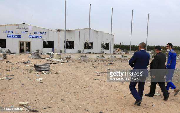 Picture taken on March 13, 2020 shows officials checking the Karbala airport in the Iraqi shrine city, one of the areas targeted by US military air...