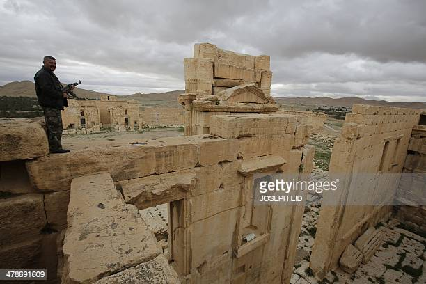 A picture taken on March 14 2014 shows a Syrian policeman standing on the sanctury of Baal in the ancient oasis city of Palmyra 215 kilometres...