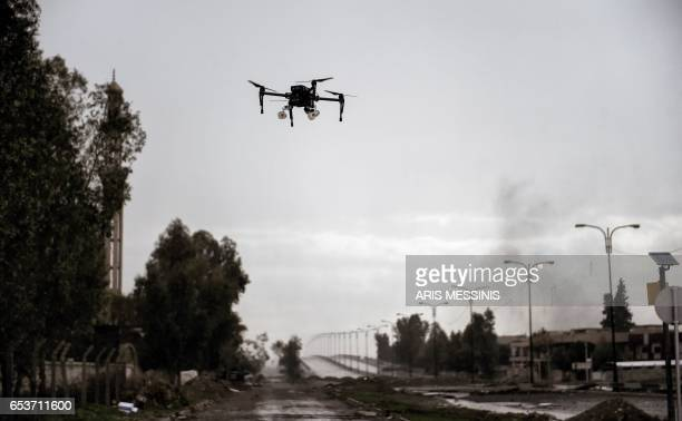 TOPSHOT A picture taken on March 14 2017 in the northern Iraqi city of Mosul shows a drone carrying two grenades flying in a test flight by Iraqi...