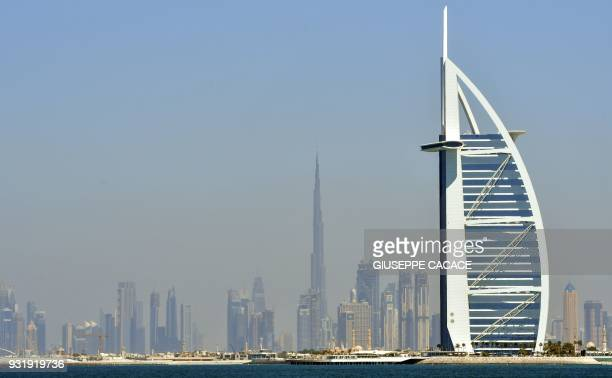 A picture taken on March 14 2018 shows the skyline of Dubai with the Burj alArab in the foreground and Burj Khalifa in the background / AFP PHOTO /...